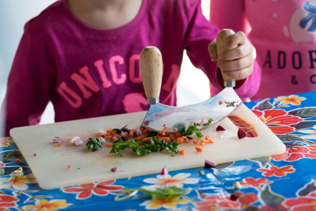 child cutting greens and carrots