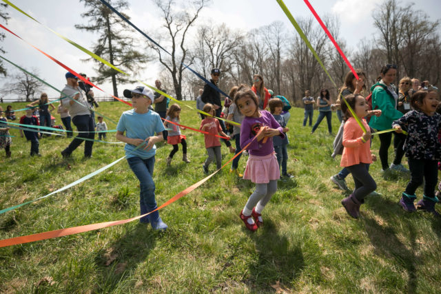 Children enjoying maypole dance in field